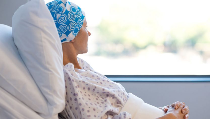 Depressed Cancer Patient Lying in Hospital Bed and Looking Outside The Window.